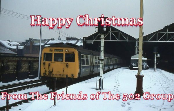"""Happy Christmas from the Friends of the 502 Group"" - with a 502 at a snow-covered Southport station"