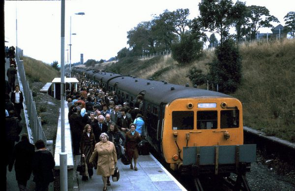 A large crowd alights from a class 502 electric